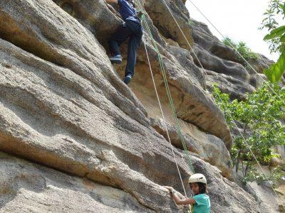 Girls climb a rock at Pandava Caves